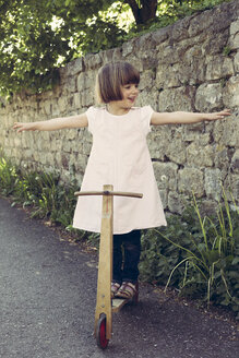 Little girl balancing on an old wooden scooter - LVF003391
