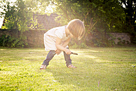 Little girl on a meadow using magnifying glass - LVF003397