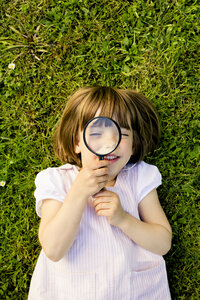 Little girl lying on a meadow looking through magnifying glass - LVF003403
