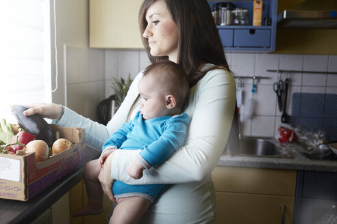 Young mother holding baby in kitchen - STKF001272