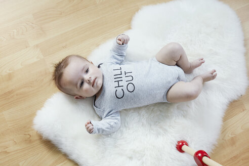 Baby lying on fur on floor - STKF001219