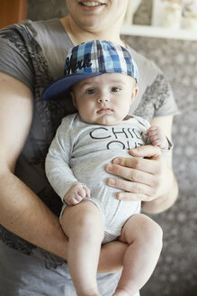 Young father holding baby - STKF001232