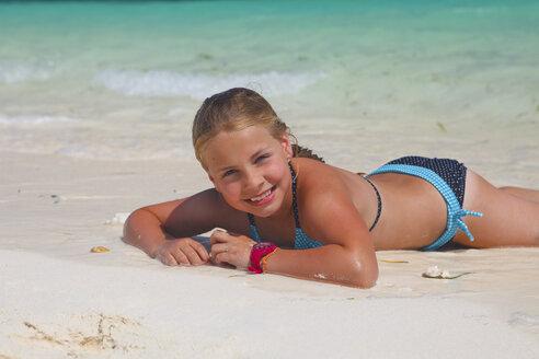 Tanzania, Zanzibar Island, portrait of girl lying on the beach at seafront - HR000019
