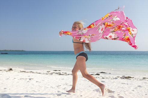 Tanzania, Zanzibar Island, girl with cloth running on the beach at seafront - HR000023