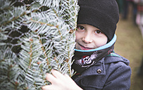 Portrait of boy with wrapped Christmas tree - ASCF000183