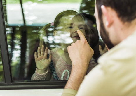 Father touching girl's nose behind car window - UUF004255