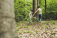 Family in forest running around tree trunk - UUF004270