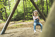 Smiling girl sitting on swing - UUF004276
