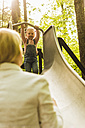 Mother looking at daughter on slide - UUF004280