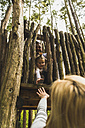 Girl  behind wooden fence reaching out for mother's hand - UUF004298