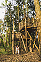 Girl sitting at tree house in forest - UUF004297