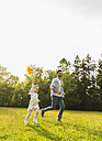 Father and daughter running with paper windmill on meadow - UUF004299