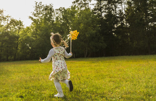 Girl running with paper windmill on meadow - UUF004302