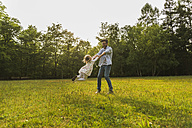 Father turning daughter on meadow - UUF004308