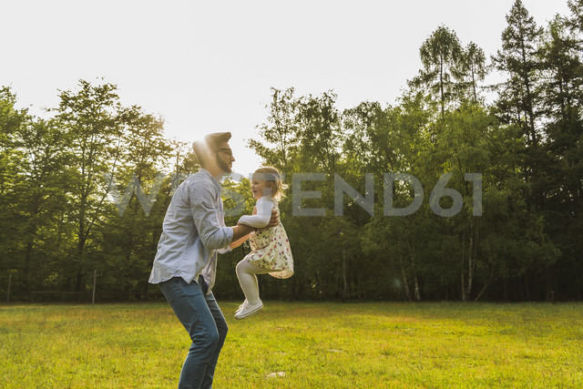 Father lifting up daughter on meadow - UUF004309 - Uwe Umstätter/Westend61