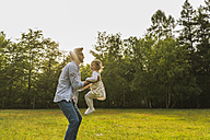 Father lifting up daughter on meadow - UUF004309