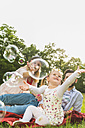 Happy family sitting on blanket in meadow catching soap bubbles - UUF004316