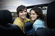 South Africa, smiling couple in convertible at the coast at sunrise - TOYF000623