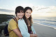South Africa, happy couple embracing on the beach at sunrise - TOYF000632