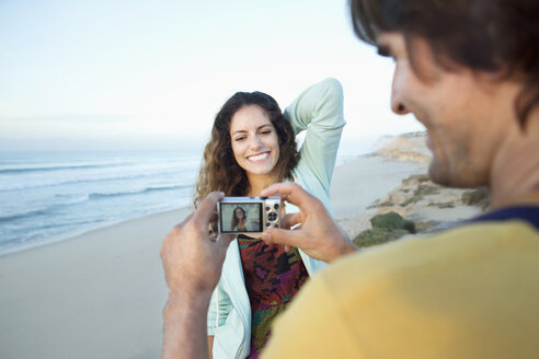 South Africa, man taking picture of girlfriend on the beach - TOYF000635