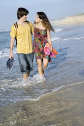 South Africa, happy couple wading in the ocean - TOYF000646