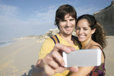 South Africa, happy couple taking a selfie on the beach - TOYF000652