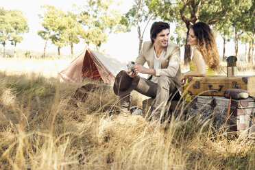 South Africa, couple sitting with suitcases at tent - TOYF000660