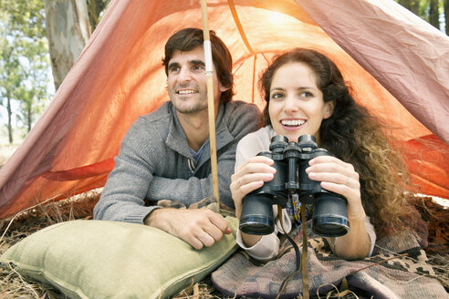 South Africa, happy couple with binoculars in tent - TOYF000672