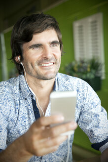 Smiling man listening to music from smartphone - TOYF000686