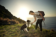 South Africa, man with dog at the coast at sunset - TOYF000805