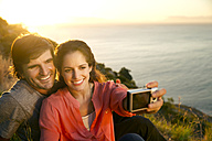 South Africa, couple taking a selfie at the coast at sunset - TOYF000709