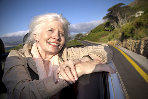 South Africa, portrait of happy senior woman sitting in a convertible - TOYF000717