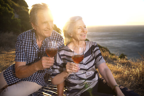South Africa, senior couple with red wine glasses looking at view - TOYF000720