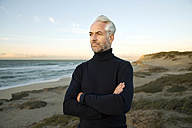 South Africa, portrait of white haired man wearing turtleneck standing on beach dunes before sunrise - TOYF000742