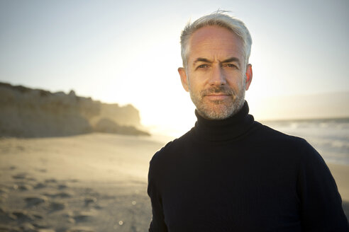 South Africa, portrait of white haired man wearing turtleneck standing on the beach  before sunrise - TOYF000751