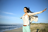South Africa, smiling woman with outstretched arms standing on the beach - TOYF000754