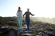 South Africa, couple walking along the coast hand in hand - TOYF000760