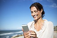 South Africa, portrait of smiling woman looking at smartphone in front of the sea - TOYF000766