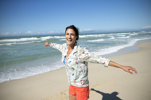 South Africa, laughing woman with outstretched arms standing on the beach - TOYF000777