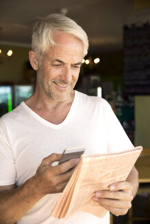 Portrait of smiling man with smartphone reading a newspaper - TOYF000789