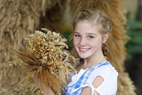 Germany, Luneburger Heide, portrait of smiling blond girl holding bunch of spikes - HRF000027