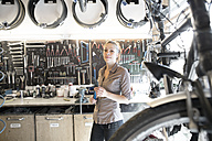 Young woman working in a bicycle repair shop - SGF001615