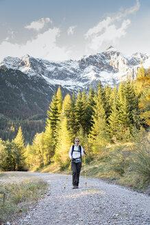 Austria, Salzburg State, Maria Alm, woman hiking in alpine landscape - NNF000346