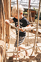 Little boy walking along hanging bridge of wooden ship on playground - MFF001622