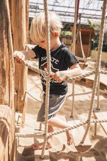 Little boy walking along hanging bridge of wooden ship on playground - MFF001622
