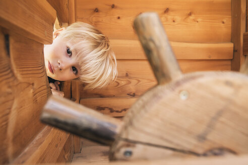 Little boy looking through hole in wooden ship on playground - MFF001627
