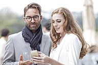 Couple with smartphone on terrace of a restaurant - ZEF005094
