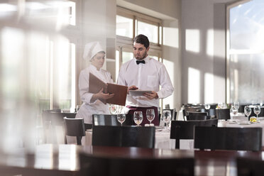Chef and waiter in restaurant discussing menue - ZEF005402