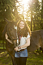 Smiling young woman with Arabian horse - SARF001804