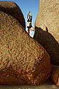Seychelles, woman standing on a rock doing yoga exercise - ABF000603